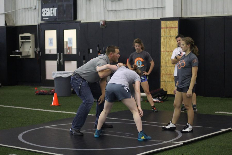 New Performance Course and wrestling coach helps freshman Brindley Eaton and sophomore Avery Ashley practice their wrestling moves. Coach Tischer deostrates on Ella Musselman as he explains the move to Eaton.