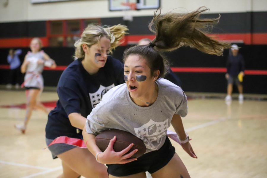 Freshman Hannah Gonzalez runs past the senior defense while senior Addison Hand attempts to grab one of Gonzalez's flags.