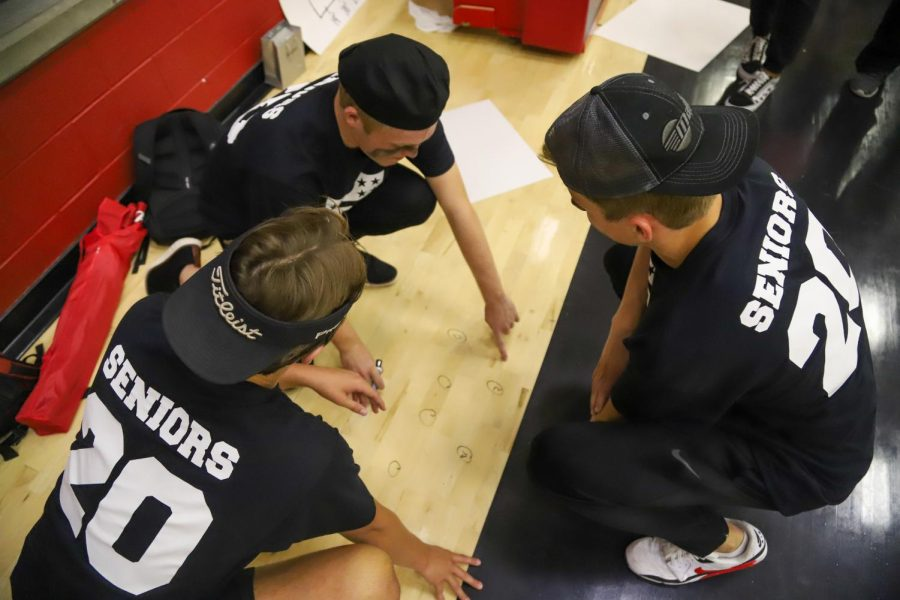 Senior coaches Harper Pool, Quinn McDermott, and Leighton Archer write out game plans on the gym floor during halftime.