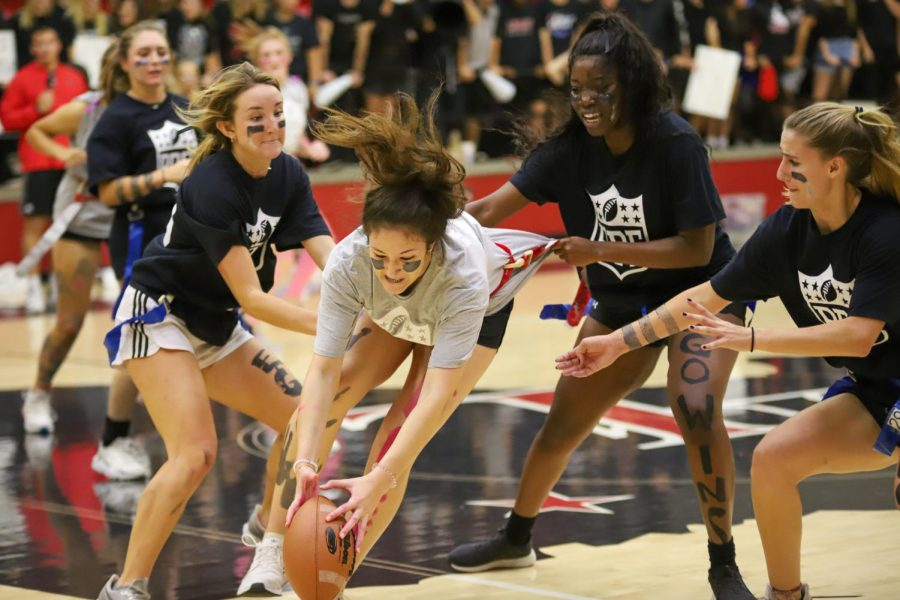 Freshman Hannah Gonzalez attempts to keep the ball in her hands while seniors Mallory Adamson, Abigail Omobogie, and Carsen McFadden grab for her flags.