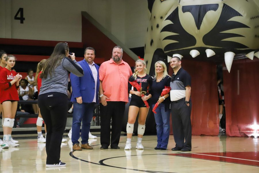 Senior+Mckenna+Franks+walks+out+with+her+family+and+psychology+teacher+John+Baker+as+she+is+recognized+during+the+volleyball+team%27s+senior+night+on+Tuesday%2C+Oct.+22.