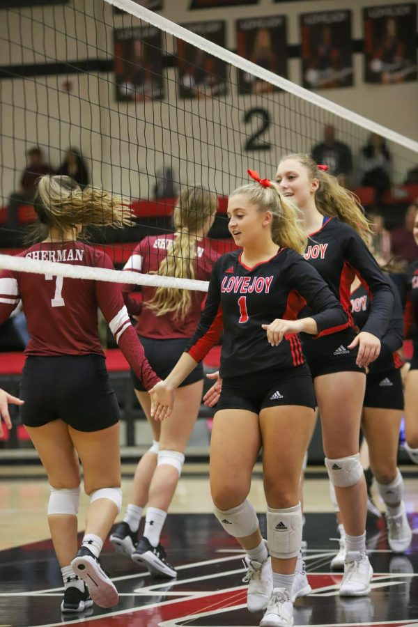 Senior Mckenna Franks leads the team as they high five their Sherman opponents before the game.