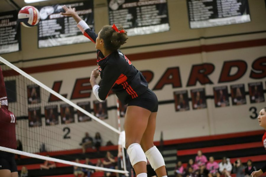 Junior Cecily Bramschreiber elevates up to hit the ball past Sherman's blockers from the outside hitter position during the first set.
