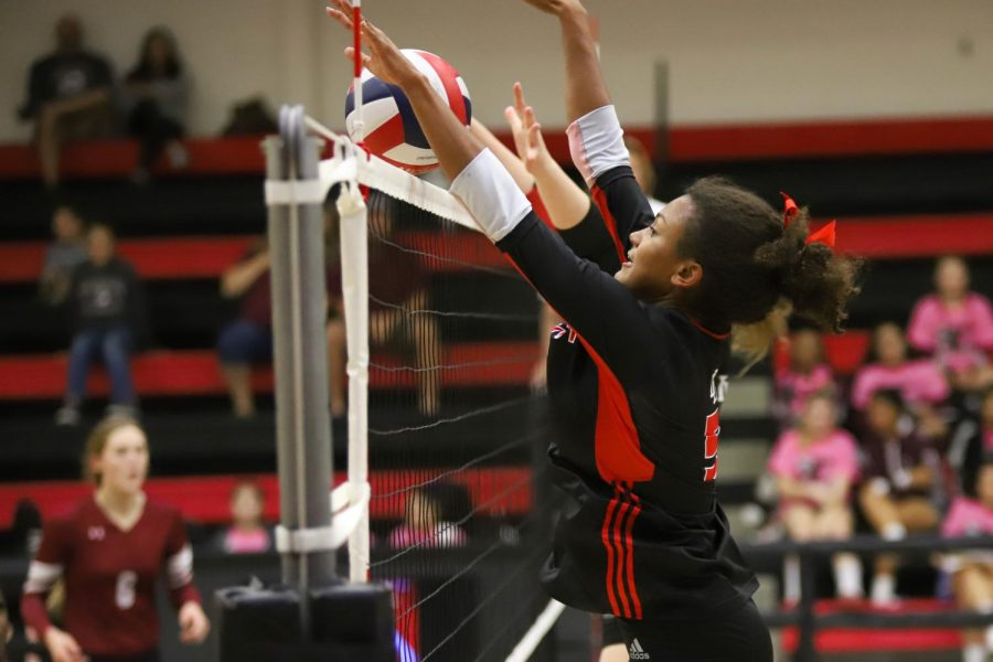 Junior Cecily Bramschreiber successfully blocks the ball from Sherman's right side hitter.