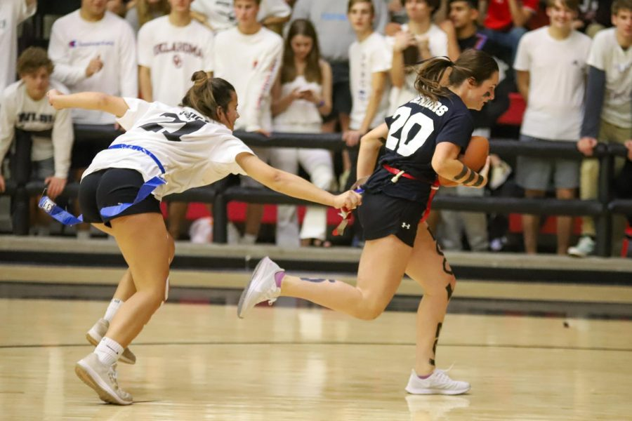Junior Callie Kemohah attempts to pull the flag of senior Mackenzie Mitchell as Mitchell heads down the court.