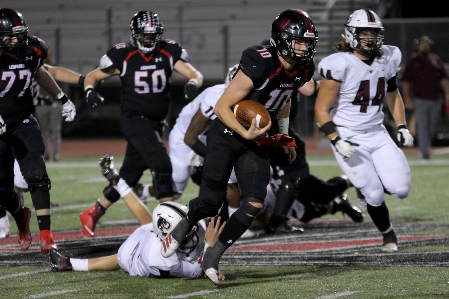Junior quarterback Ralph Rucker (10) scampers across midfield after escaping the passer's pocket. Rucker leads the Leopards this season in both passing and rushing yards.
