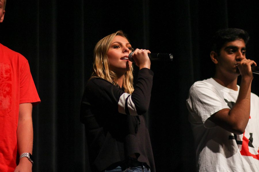 Senior a cappella member Colette Brooks holds up the microphone while singing