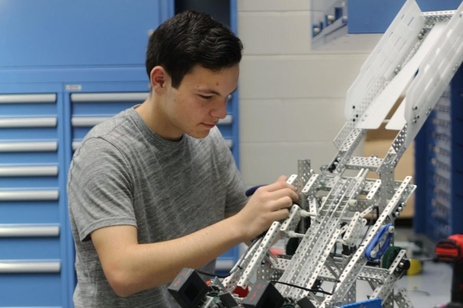 Sophomore Daniel Hanna adjusts his robot during his Robotics 3 class. He will compete in the competition in Austin this weekend.