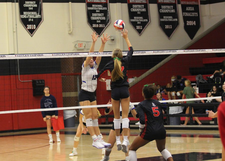 Sophomore+Rosemary+Archer+elevates+the+ball+on+to+the+other+side+of+the+net+before+a+block+by+Aledo.+