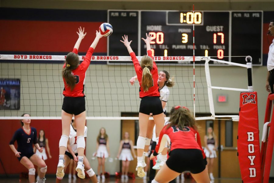 Junior Lexie Collins and sophomore Averi Carlson jump to block the ball from Frisco Centennial's outside hitter.
