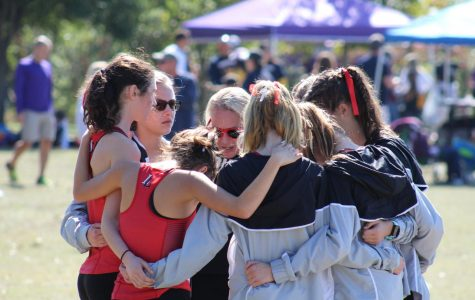Coach Carly LIttlefield talks with the girls team before they head to the starting line to race.