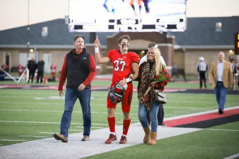 Before the game, seniors who participate in football, sports medicine, band, majestics, cross country, golf, and swim walked across the field as their names were announced on senior night. Senior football athlete Quinn McDermott walks with his parents across the field.