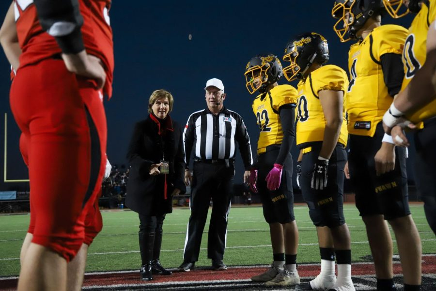 State representative Candy Noble flips the coin as Lovejoy and Denison athletes watch. The coin flipped to the heads side.