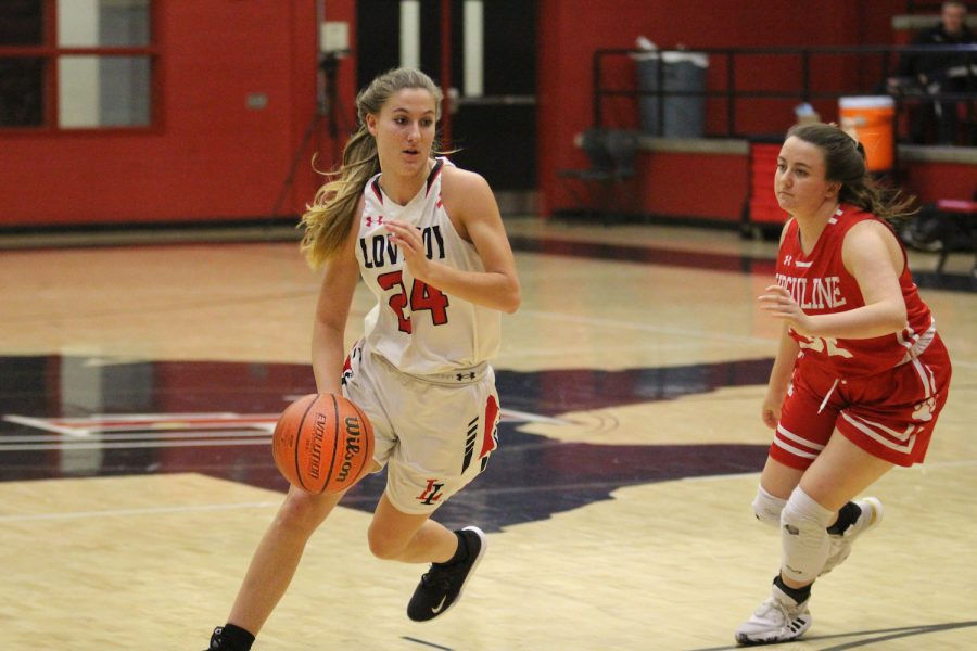Senior Carsen McFadden dribbles the ball around one of Ursuline's players. The Leopards won the game by one point.