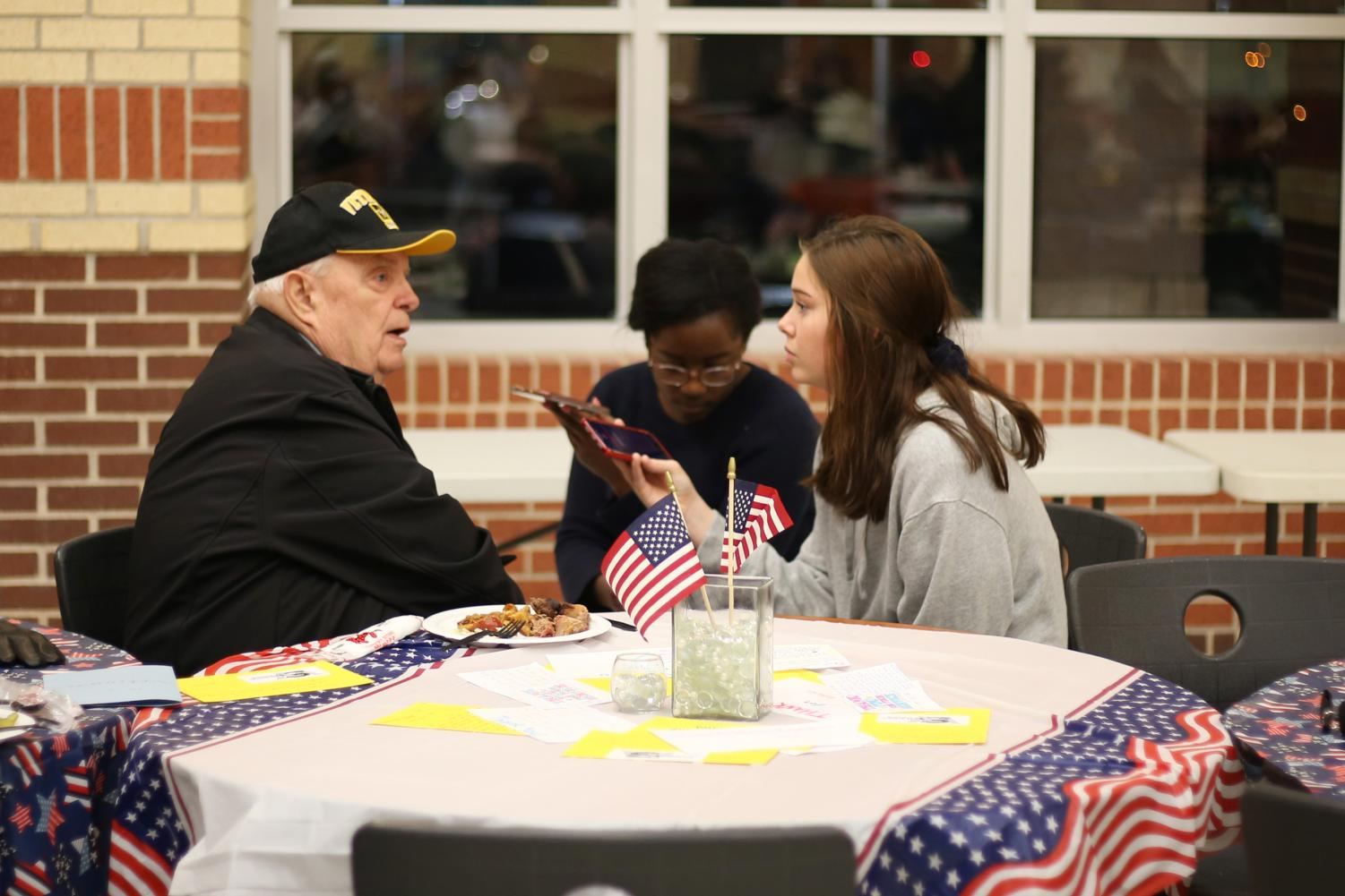 Korean War veteran William Larry O'Brien talks with reporters Suvwe Kokoricha and Lindsey Hughes.