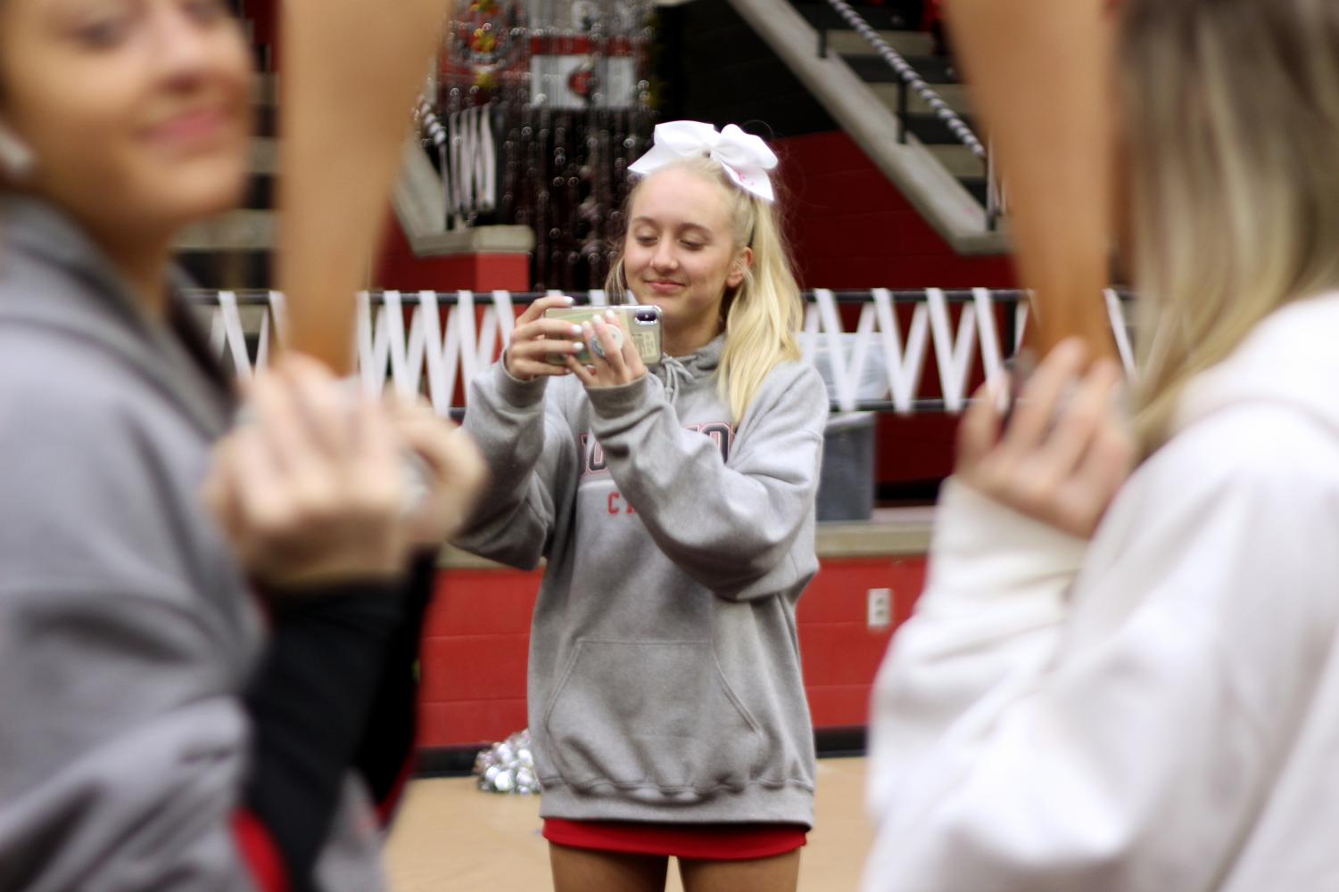 Sophomore Taylor Pickett films a stunt for the newest video on the Lovejoy Cheer Vlogs youtube channel.