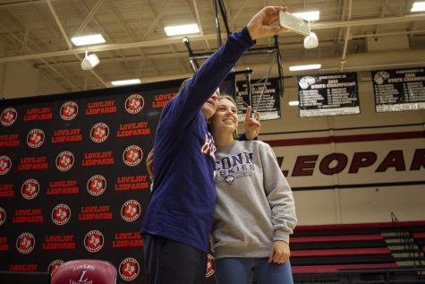 Senior Ana Laura Faoro takes a selfie with a family member following the signing.