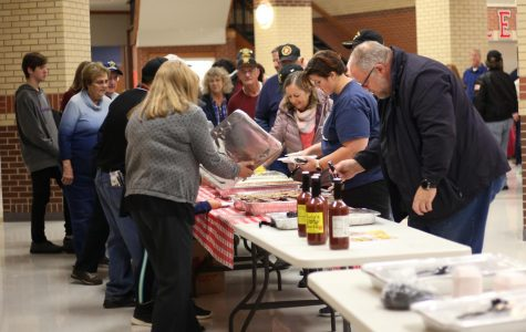 The Veterans get in line to prepare their dinner plate. The Student Council served Rudy's for the veterans.