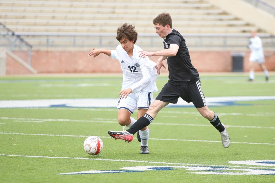 Junior Michael Myers battles for possession against Flower Mound's Sebastian Palma.