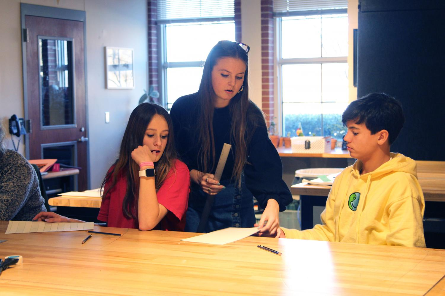 Art 1 teacher Cassidy Fuller assists students in class. Fuller shares her classroom part time with the teacher she once learned from as a student at Lovejoy.
