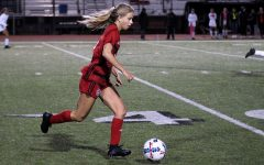 Junior Hannah Dunlap dribbles the ball to look for left wing Reagan Matacle. Dunlap assisted the Leopard's goal in the first half.