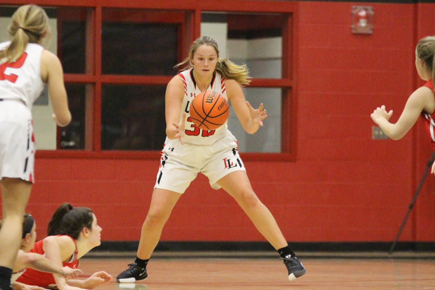 Senior Addison Hand grabs the basketball after junior Julia Brochu tosses the ball up to her.