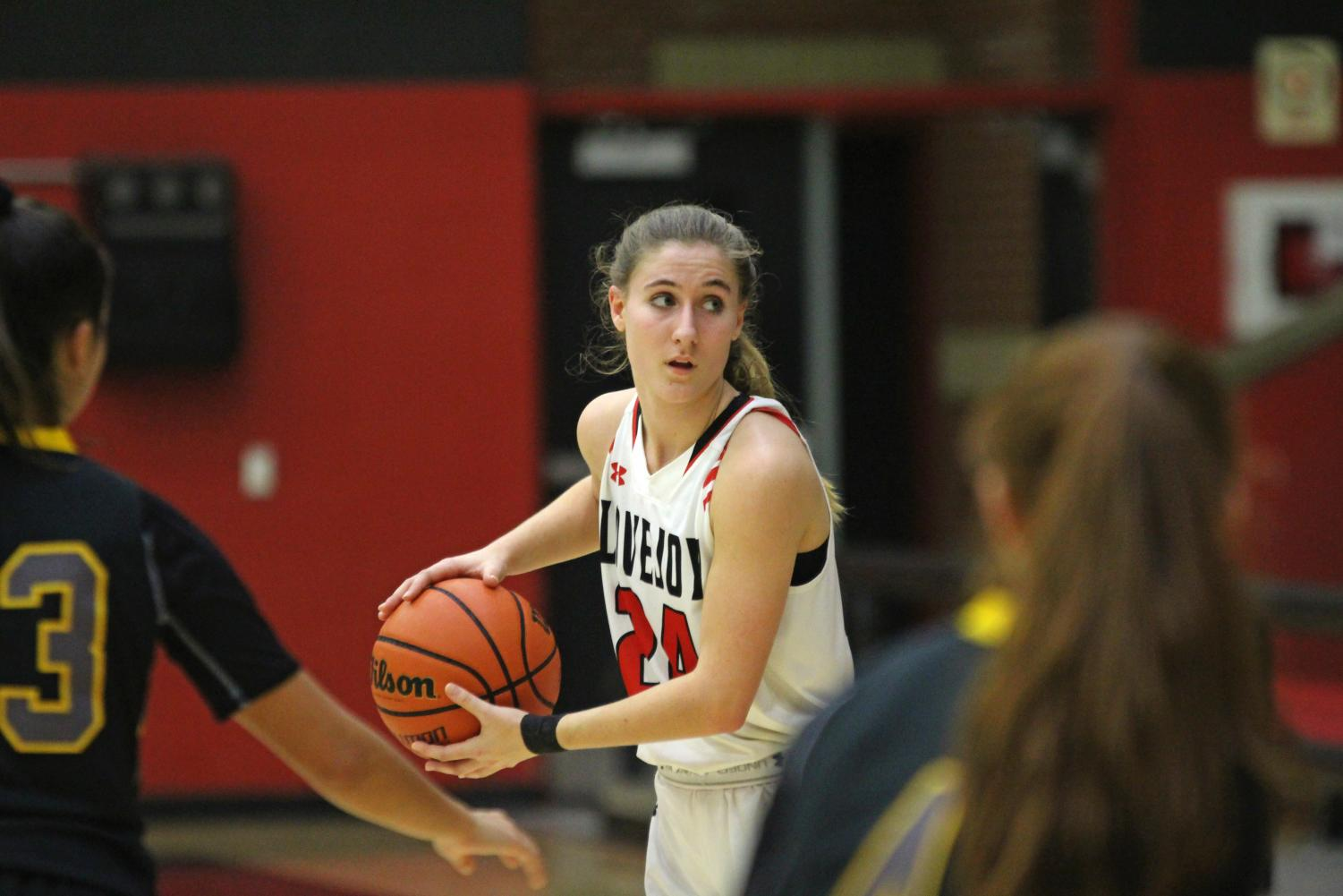 Senior Carsen McFadden looks to drive to the lane and dump the ball to senior Carly Ludlow for a basket.