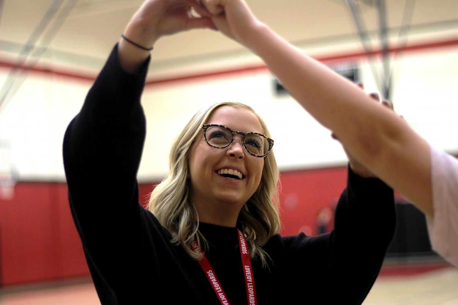 New JV cheer coach and leadership teacher Ms. Pikl, corrects a cheerleader's arm positioning. Before coming to the school she taught in Oklahoma.
