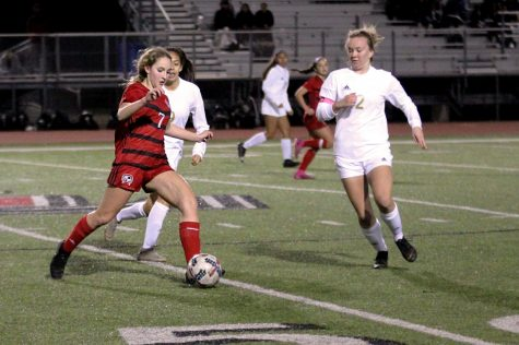 Sophomore Tatum Chester dribbles around two of The Colony