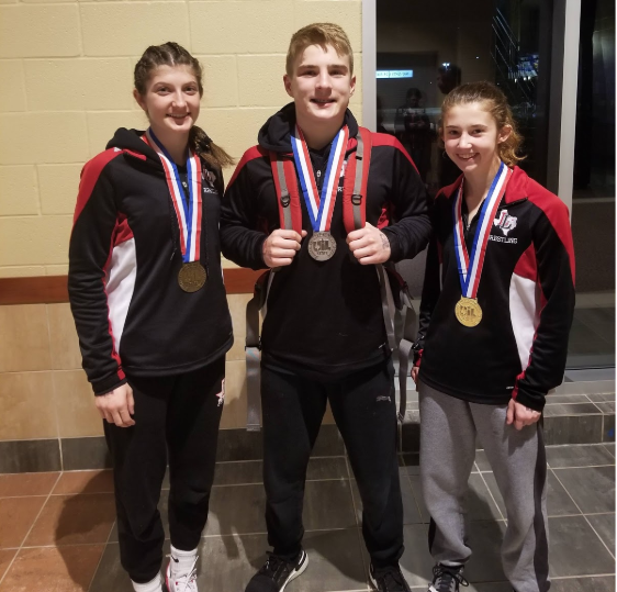 Wrestlers Katherine Heath, Alex Vislosky and Avery Ashley (left to right) finish the UIL wrestling season as winners in their weight classes.