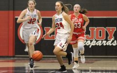 Senior Carsen Mcfadden dribbles the ball past half court in a game against Ursuline.
