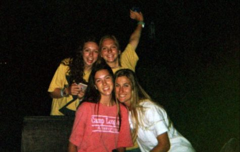 Seniors Olivia Porsch, Madeline Sanders, Lily McCutcheon and Carsen McFadden gather around a bonfire in June after returning from camp.