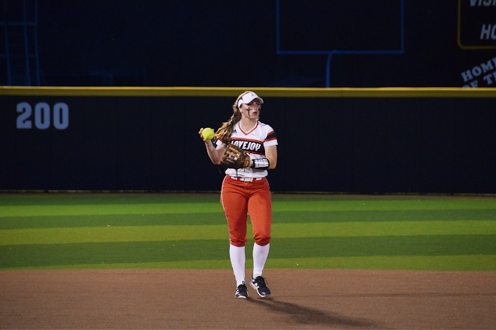 Senior Leah Taylor checks first before throwing the softball in a game against Royse City.