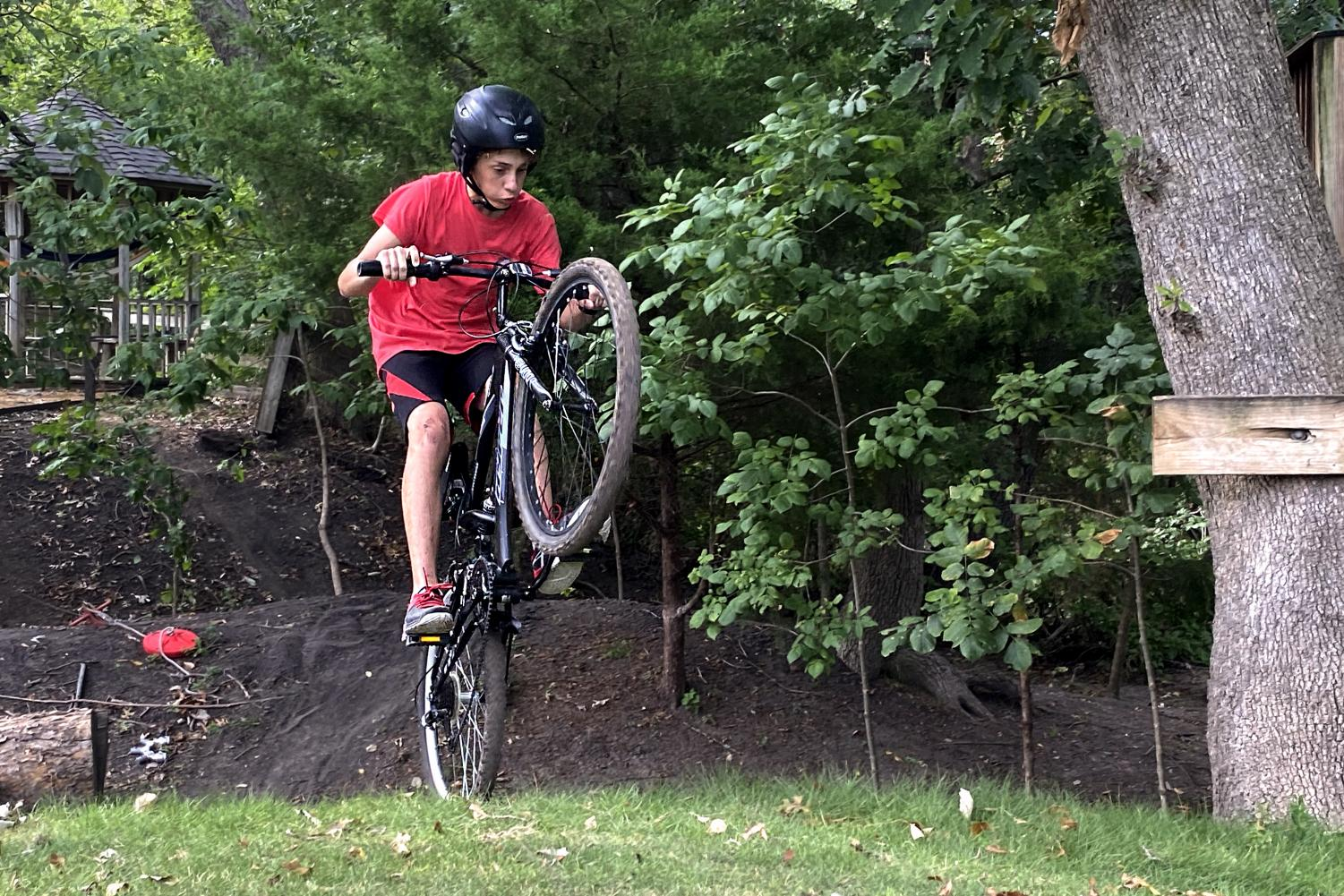 Sophomore Luke Farkas pops a wheelie after riding up a hill. It took Farkas about 50 hours to build the course.