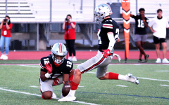 Junior running back Noah Naidoo holds the ball for a kick by junior Trent Rucker. The extra point was good after junior Philip Joest ran in the ball for a touchdown.