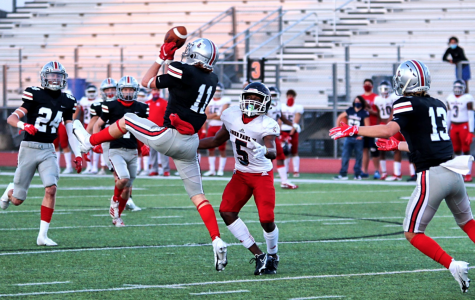 Senior safety Chief Collins elevates to intercept a pass from John Paul II's quarterback Hayden Ferguson in the opening drive. John Paul II threw four interceptions in the game.