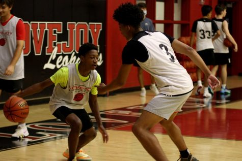 Junior Taiden Conner dribbles the ball for a basketball drill. The boy