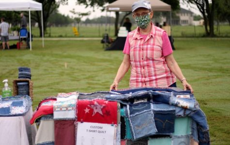 Kay Montgomery stands with her custom jean quilts. She uses old worn out jeans to create quilts, potholders, and other items.