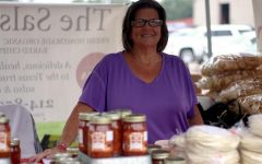 Stephanie Canada stands behind The Salsa Texan's products for sale at the Lucas Farmer's Market. She is one of a few sales representatives around the area for The Salsa Texan.