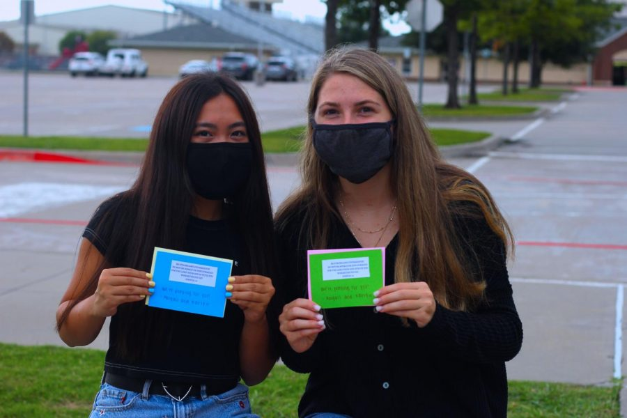 Seniors Karly Greenwood and Abigail Le hand out prayer cards to the community. They can be seen at school facilities, Grand Brook Memory Care, and the Lucas Fire Department.