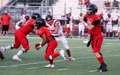 Junior Noah Naidoo runs to block for his teammate while senior Ralph Rucker completes a pass to Sophomore receiver Jaxson Lavender. Naidoo is the Leopard's starting running back.