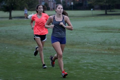 Freshmen Caroline Dolberry and Senior Karly Greenwood run at a team practice. The cross country team practices together at Celebration Park.