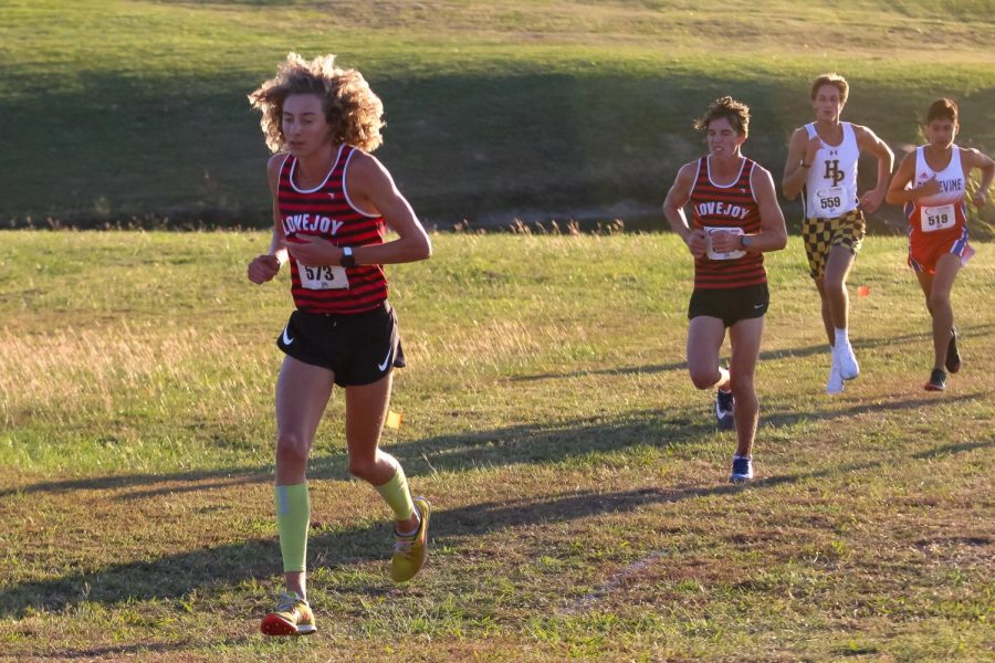 Junior Tate Barr runs up a hill at Myers Park. The high school cross country team won districts in all four races.