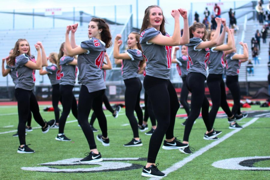 Senior Majestics Alexa Barajas, Alex McCaffity, Sydney Spors and Meredith Hughes dance during their pep rally performance. The Majestics wore football jerseys during their performance with the numbers of their football buddies.