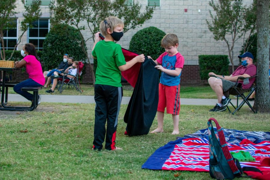 Two younger brothers of an orchestra member put out a blanket to sit on to listen to the concert on. Many children attended the courtyard concert.