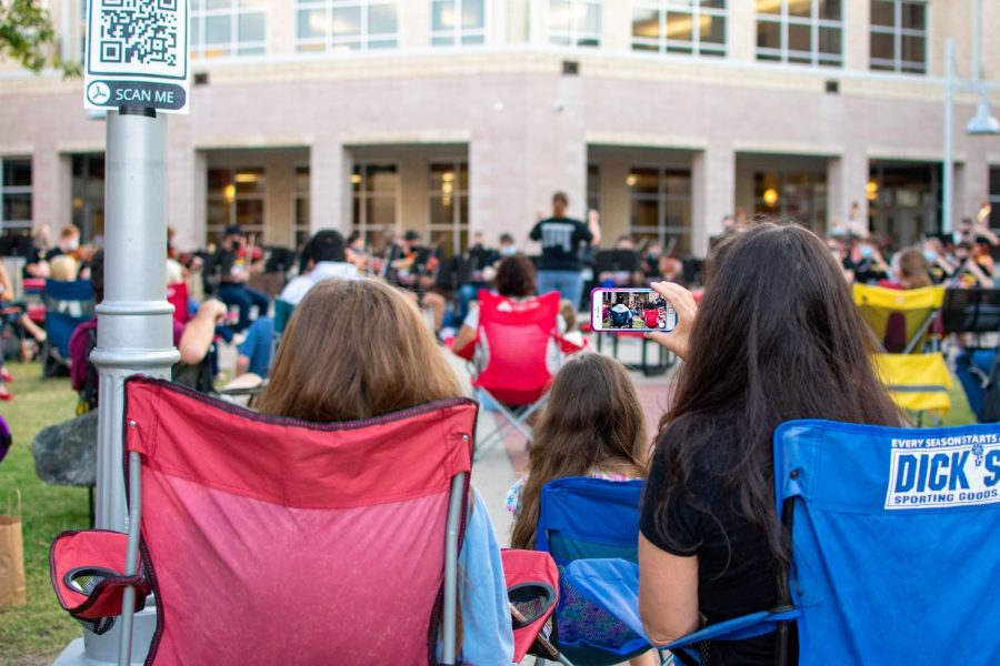 A mom videos the performance from her lawn chair. There were QR codes placed around the courtyard for the performance.