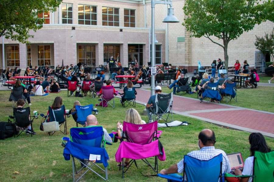 Parents and community members sit socially distanced in the high school courtyard. This concert style was provided to let families and friends listen to the orchestra while keeping a safe distance.