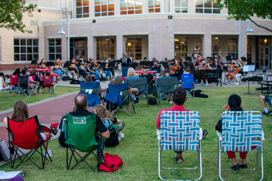 People sit in the grass of the high school courtyard to watch the concert. There were four different performances for the different orchestra classes.