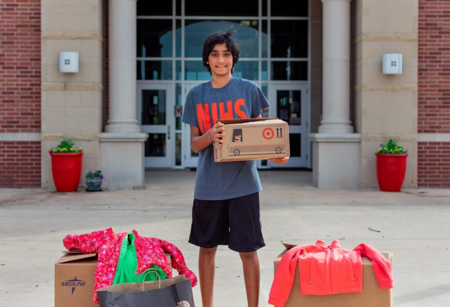 Eighth-grader Dylan Mori stands with some of his collected donations. Mori is collecting clothes, shoes, food items, and diapers for his drive.