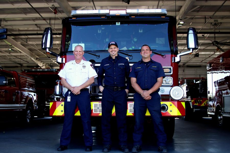Fire Chief Ted Stevens, Fire Captain Ethan Carver, and Paramedic Michael Dunnam stand at the front of one of their fire engines inside their station. The three work together for the Lucas Fire Department.